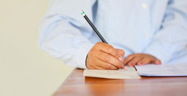Prenez le dernier examen lycéen tenant un crayon écrit sur une feuille de réponses Photo Premium