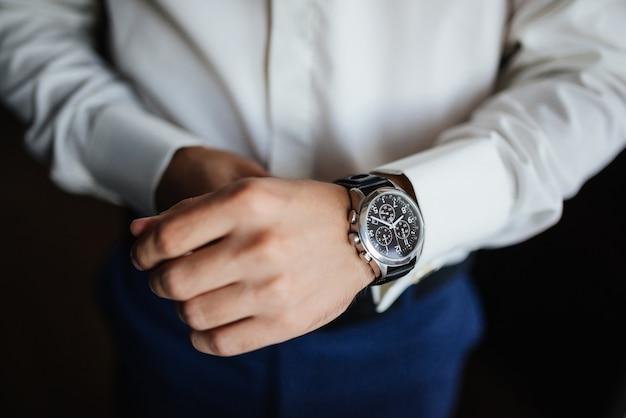 Préparation aux répétitions. la montre du marié à portée de main. Photo gratuit