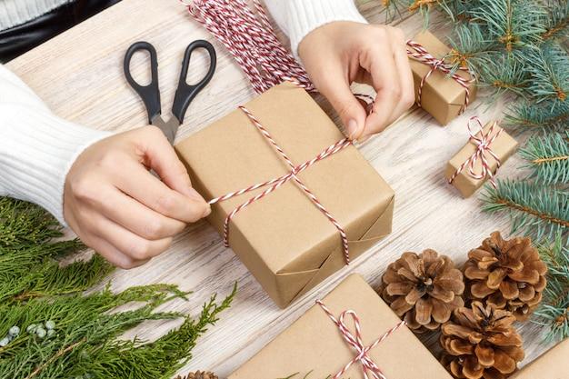 Préparation de cadeaux de noël, boîte-cadeau emballée dans du papier à rayures noir et blanc, une caisse pleine de pommes de pin et de jouets de noël et du matériel d'emballage sur du vieux bois blanc Photo Premium