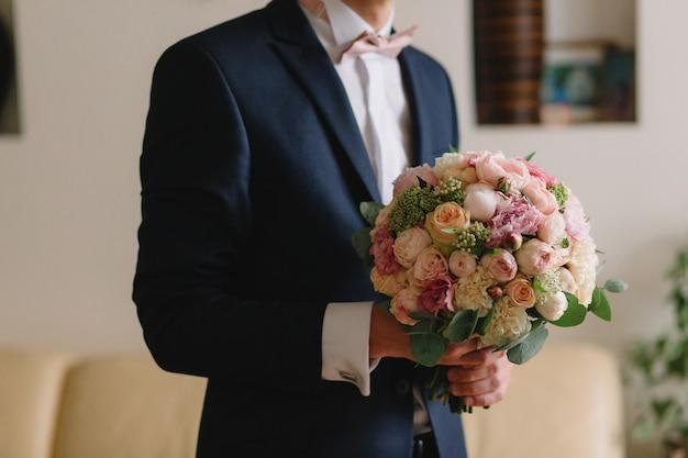 Préparation du mariage matin du marié. jeune et beau marié s'habiller dans une chemise de mariage. Photo Premium