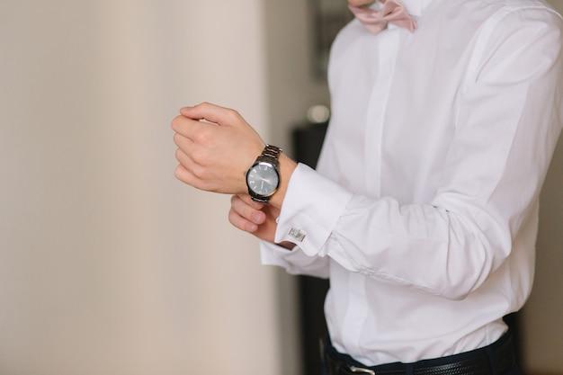 Préparation du matin du mariage. gros plan des mains du marié en chemise blanche, ajustant le poignet Photo Premium