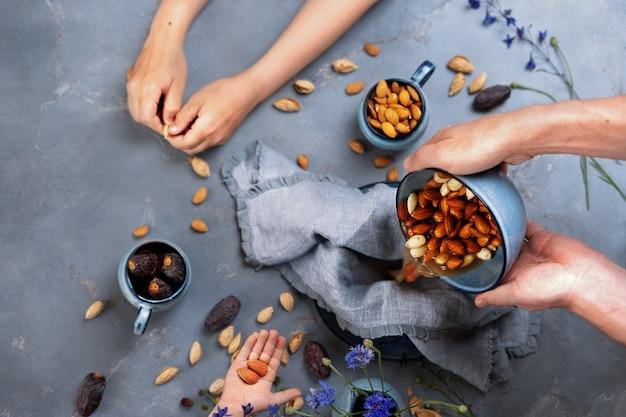 Préparation De Lait D'amande Maison. Les Mains Des Hommes Tiennent Un Bol Avec Des Graines D'amande Photo Premium