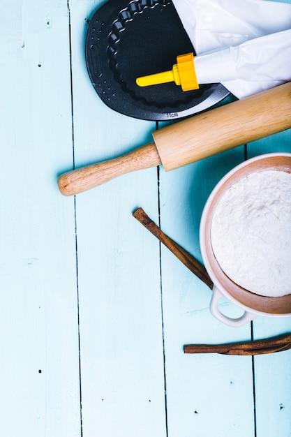 Préparation de la pâte. ingrédients pour la pâte - œufs et farine au rouleau. sur fond en bois Photo Premium