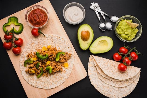 Préparation de tacos sur une planche à découper près de légumes et de sauces Photo gratuit