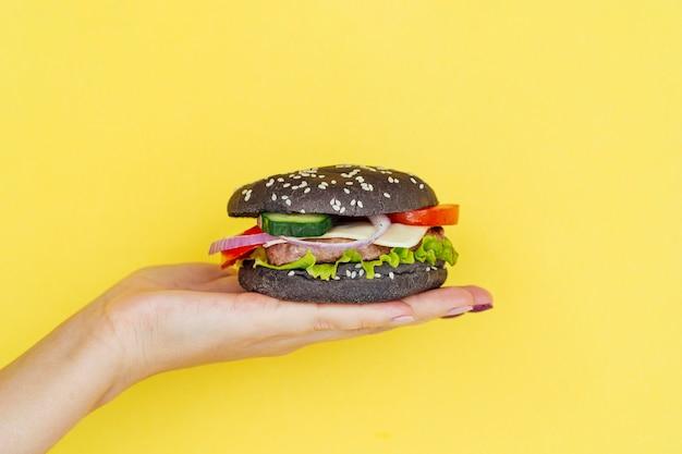 Présentation de la main cheeseburger savoureux Photo gratuit