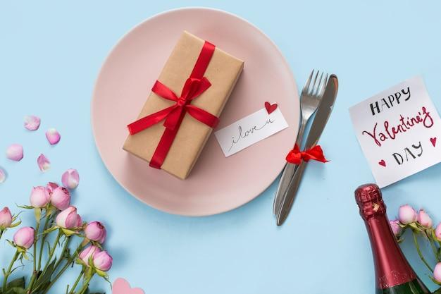 Présenter une boîte sur une assiette entre des couverts, une bouteille et des fleurs Photo gratuit