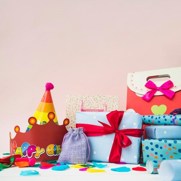 Présenter des boîtes avec des couronnes; ballons et sacs à provisions sur fond rose Photo gratuit