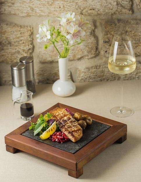 Présentoir en bois avec filet de poisson grillé et légumes Photo gratuit