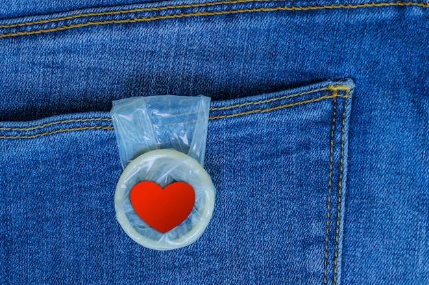 Préservatif Avec Un Cœur Rouge Suspendu à Une Poche De Jean. Amour Et Romance. Sexe Sans Risque. Carte De La Saint-valentin. Photo Premium