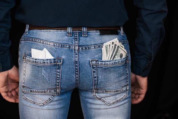 Préservatifs et billets de banque dans les poches arrières des jeans pour hommes Photo Premium