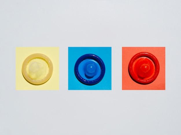 Préservatifs colorés à plat sur fond blanc Photo gratuit