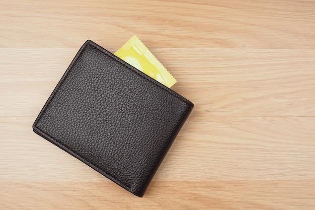 Préservatifs jaunes dans un portefeuille noir sur fond de table en bois Photo Premium
