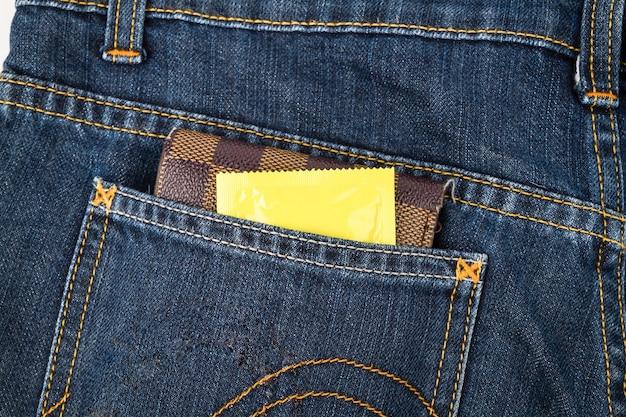 Préservatifs et porte-monnaie dans la poche de jeans Photo Premium