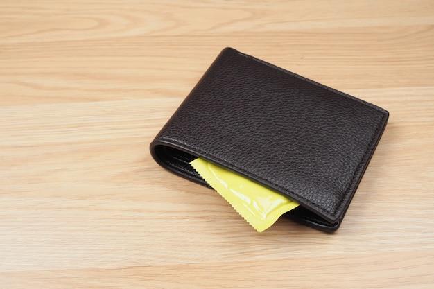 Préservatifs en portefeuille noir sur fond de table en bois Photo Premium
