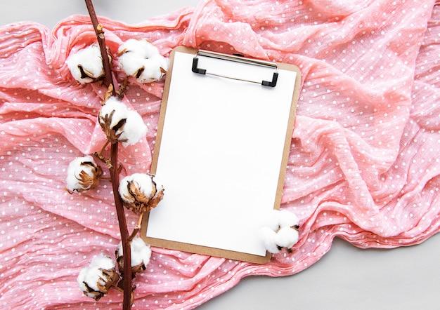 Presse-papiers à accessoires de bureau arrangés stylisés, fleurs en coton, foulard. accessoires de mode pour femmes. plat poser vue de dessus Photo Premium