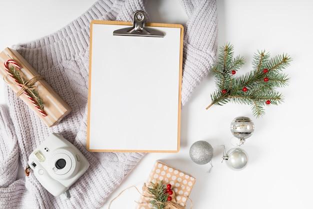 Presse-papiers avec boîtes-cadeaux et branches vertes Photo gratuit
