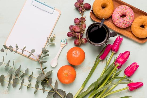 Presse-papiers à cadre avec pause café sucrée et fleurs Photo gratuit