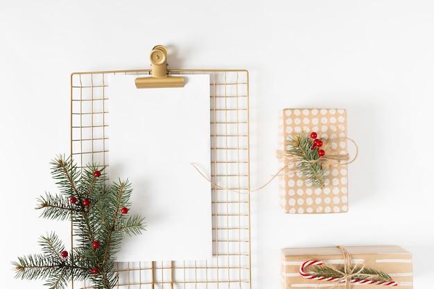 Presse-papiers avec coffrets cadeaux sur table blanche Photo gratuit