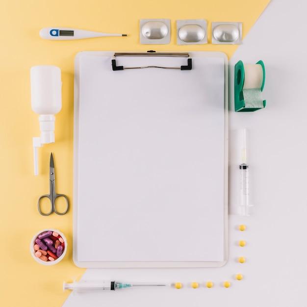 Presse-papiers avec du papier blanc vierge entouré d'équipements médicaux sur fond bicolore Photo gratuit