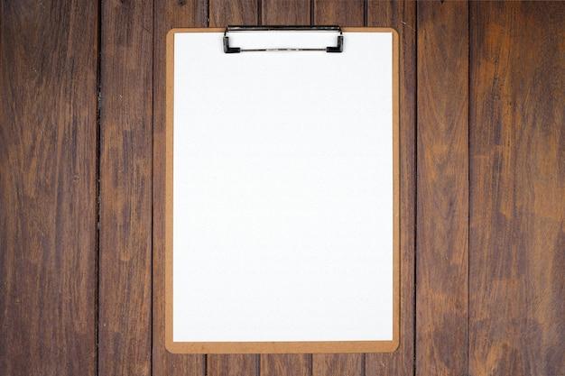 Presse-papiers avec feuille blanche sur fond de bois marron Photo Premium