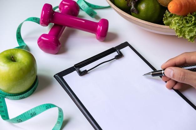 Presse-papiers avec fruits sains, légumes et ruban à mesurer sur le bureau du nutritionniste, bonne nutrition et alimentation Photo Premium