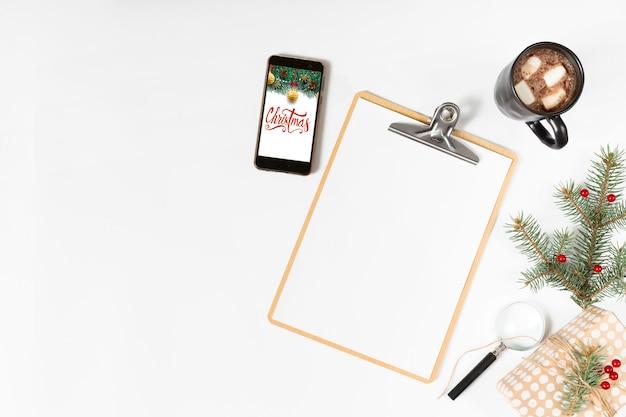 Presse-papiers avec inscription de noël sur l'écran du smartphone Photo gratuit