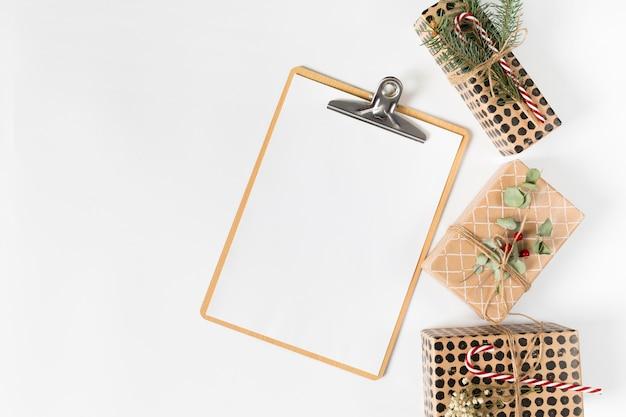 Presse-papiers avec petites boîtes-cadeaux sur une table lumineuse Photo gratuit