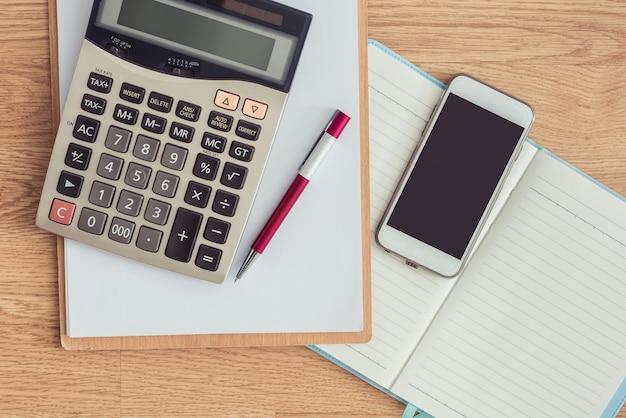 Presse-papiers Avec Un Stylo Et Un Cahier, Calculatrice Sur La Table De Bureau Photo Premium