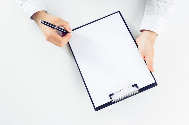Presse-papiers sur une table blanche. fermer Photo Premium