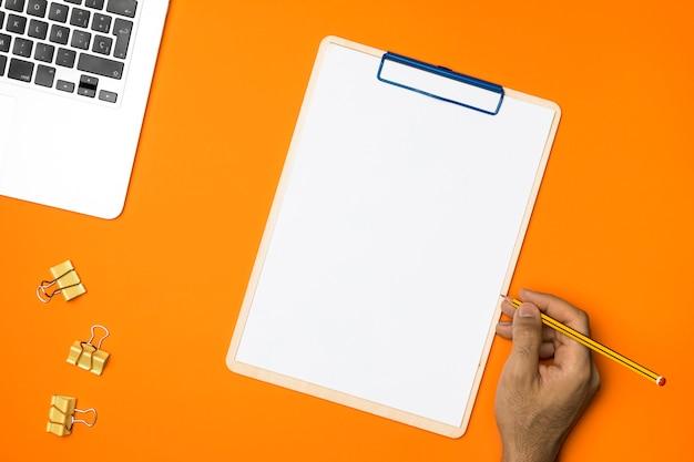 Presse-papiers vide plat lay avec fond orange Photo gratuit