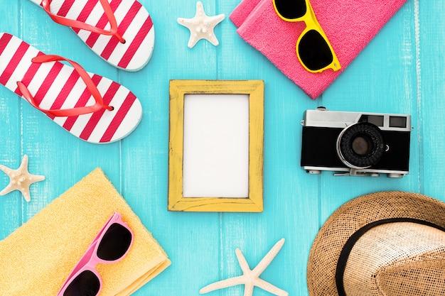 Prêt pour des vacances à la mer: serviette, lunettes de soleil, hart, appareil photo, monture et crème solaire Photo gratuit