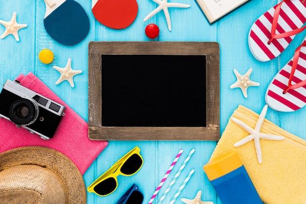 Prêt pour des vacances à la mer: serviette, lunettes de soleil, tableau noir et crème solaire Photo gratuit