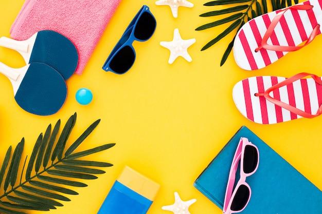 Prêt pour des vacances à la mer: serviette, lunettes de soleil, tongs, feuilles, étoile de mer et crème solaire Photo gratuit