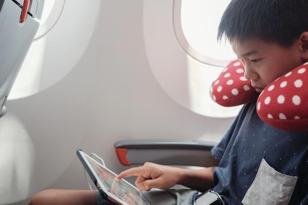 Preteen asiatique utilisant une tablette en vol, famille voyageant à l'étranger avec des enfants Photo Premium