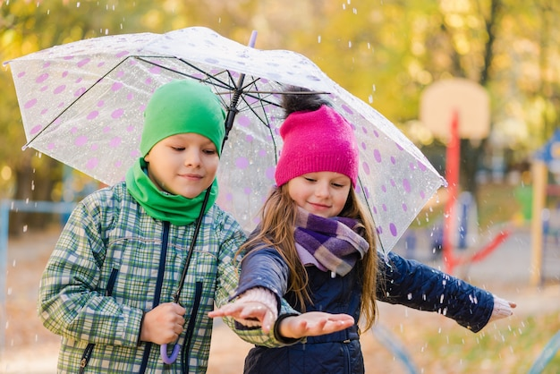 Preteen Boy And Girl Walk In Rainy Park Extérieur Photo Premium