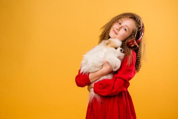 Preteen fille tenant un petit chien dans ses mains Photo Premium