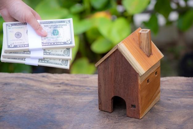 Prêts pour la main de concept immobilier tenant un argent et une maison modèle mis en place dans le parc public Photo Premium