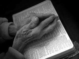Priant les mains sur la bible - en noir et blanc Photo gratuit