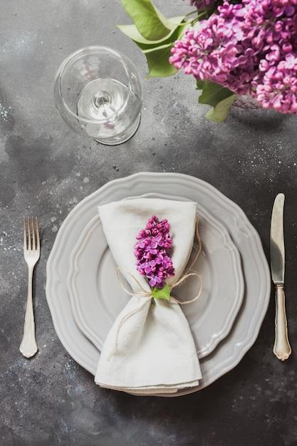 Printemps élégant cadre de table avec violet lilas, couverts sur table vintage. Photo Premium