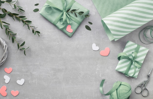 Printemps plat poser avec des boîtes-cadeaux, des coeurs et des feuilles d'eucalyptus Photo Premium
