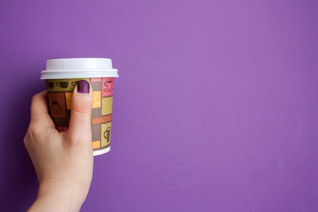 Prise de main de femme prend un café devant le mur violet Photo Premium