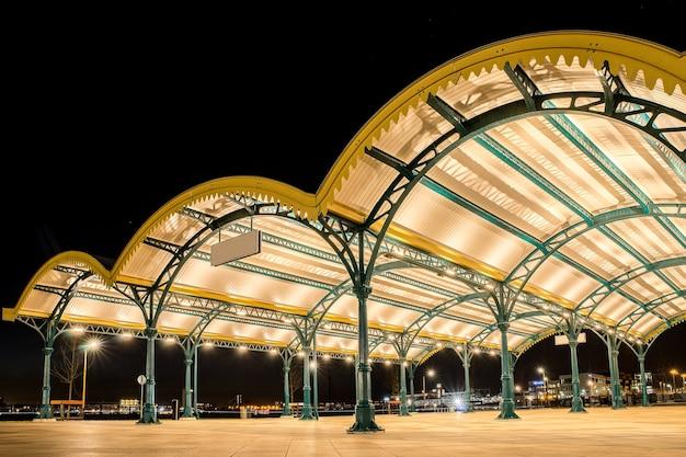 Prise De Vue En Angle De Trois Toits Incurvés Jaunes Dans Une Ville Avec Des Lumières Sous Un Ciel Sombre Photo gratuit