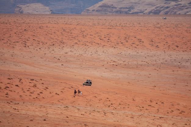 Prise De Vue Au Grand Angle De Deux Personnes Sur Des Chameaux S'approchant D'une Voiture Dans Un Désert Photo gratuit