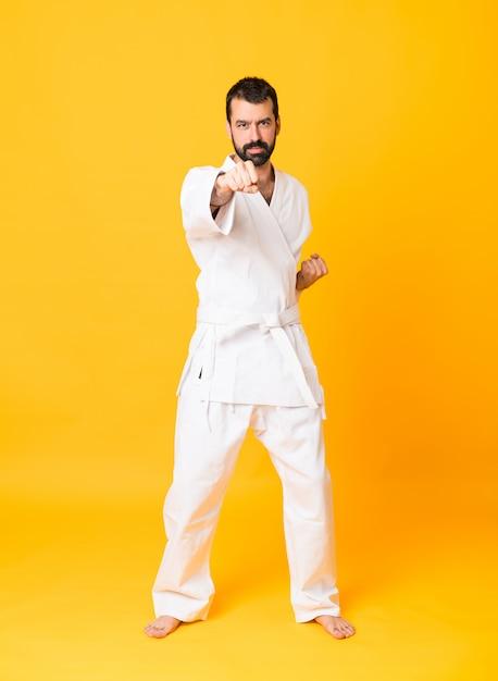 Prise de vue complète de l'homme au karaté isolé jaune Photo Premium
