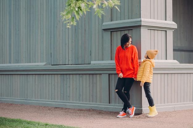 Prise de vue en extérieur d'une femme amicale tient la main de sa fille Photo Premium