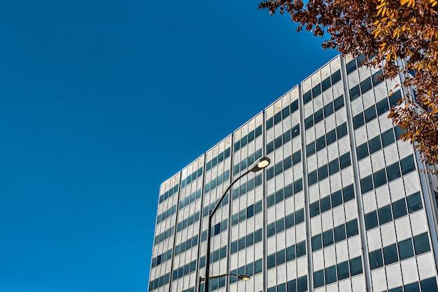 Prise De Vue à Faible Angle D'un Grand Bâtiment En Verre Près Des Arbres Sous Un Ciel Bleu Nuageux Photo gratuit