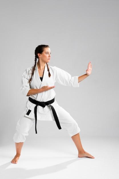 Prise de vue d'une femme à la ceinture noire et kimono pratiquant le karaté Photo gratuit