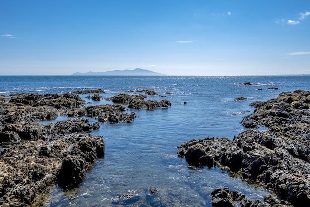 Prise De Vue En Grand Angle De Formations Rocheuses Dans L'eau De La Baie De Pukerua En Nouvelle-zélande Photo gratuit