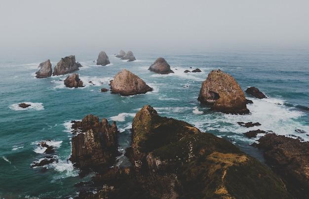 Prise De Vue En Grand Angle De Gros Rochers à Nugget Point Ahuriri, Nouvelle-zélande Avec Un Fond Brumeux Photo gratuit