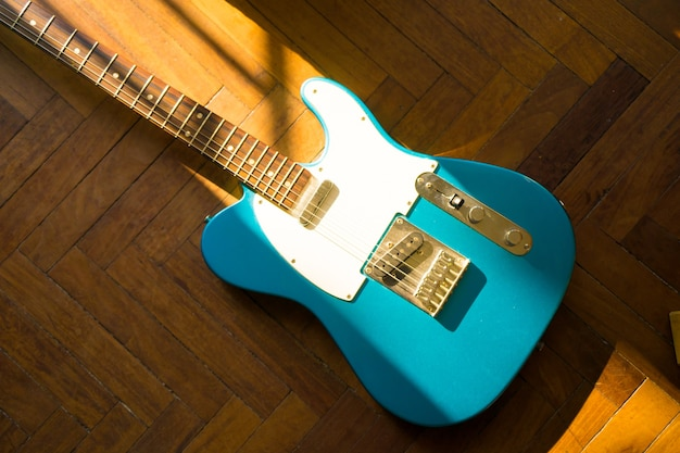 Prise De Vue En Grand Angle D'une Guitare Bleue Sur Une Surface En Bois Photo gratuit